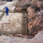 Ground anchors projecting into ground beam reinforcement
